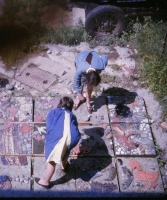 A view taken from above shows blocks to the right which have been completed and a block with shuttering in the centre where the girls are working into the wet cement. Stones are still being arranged on other blocks.