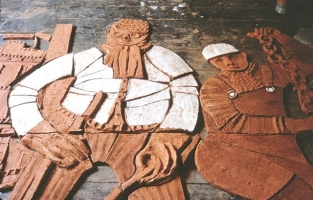 The figures of two steel workers are seen lying on the studio floor. One wears goggles and the other holds a heavy chain. The clay has been biscuit fired so appears terracotta, and awaits the application of glazes and further firing.