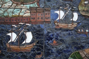 A detail: little rowing boats ply across the river with sailing ships in full sail.
