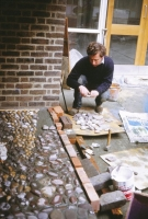 Kennedy lays stones into the wet cement render.  We organise the backing stones into drifts and layers to give a consistent but lively background to the different figures.