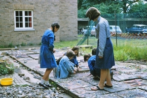 Here I am seen encouraging a group of small children as they arrange their pieces of ceramic and stone into the cement render. Only the youngest children worked in class.  All the older girls worked on the mural on a voluntary basis in their own time.